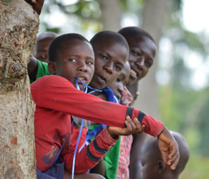 children peeking from behind a tree